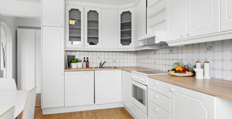 Kjøkkenet har hvitmalt innredning med profilerte fronter. Ny benkeplate i 2019