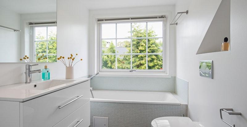 Lyst og tiltalende bad fra 2009 med badekar og egen dusjnisje