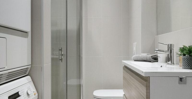 Badet har varmekabler i gulv og inneholder servant, dusjhjørne, vegghengt wc og opplegg til vaskemaskin/tørketrommel.
