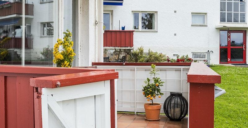 Verandaen har trapp som fører med til en terrasseplatting og til plenen