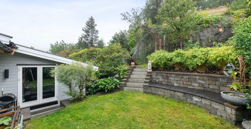 Det er over flere år lagt et betydelig arbeid i utformingen av hagen, her er det f eks laget 2 støttemurer, steinplatting, stentrapp opp til gressplen samt flere flotte tretrapper opp til hagens ulike nivåer.