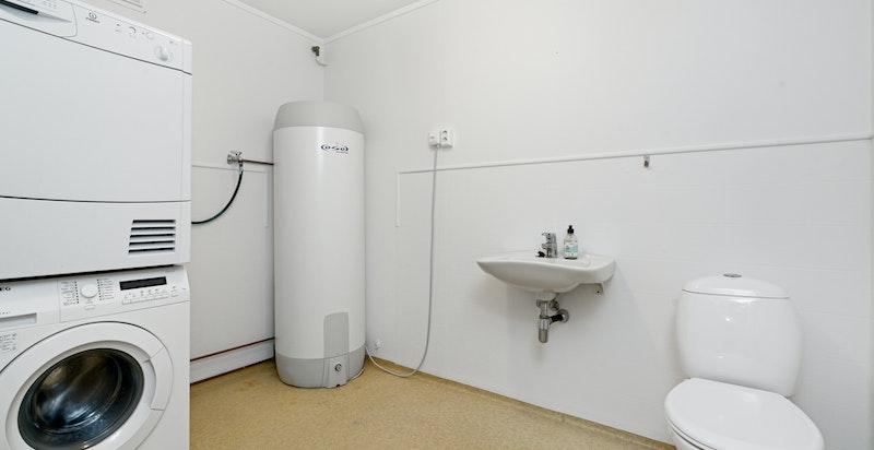 Stort vaskerom innredet med toalett og servant. Opplegg for vaskemaskin og tørketrommel.