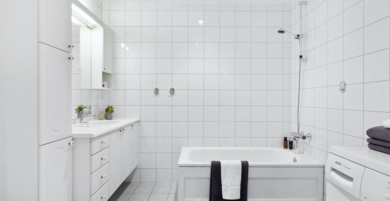 Hovedbadet er innredet med badekar, stort baderomsskap, servantskap og toalett