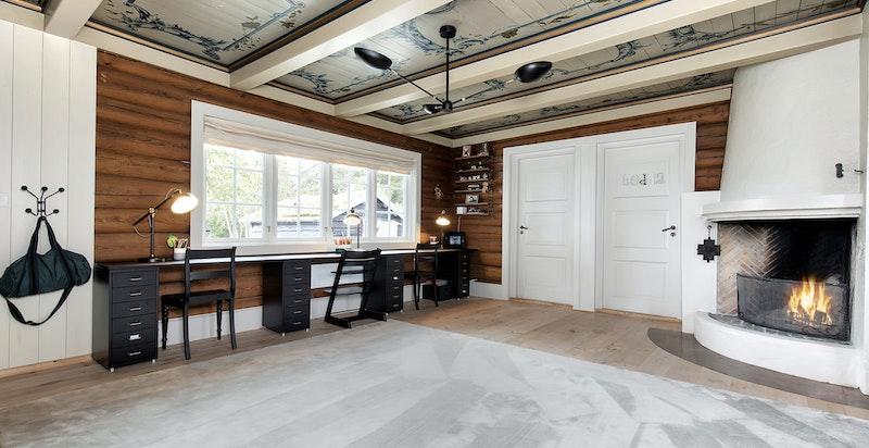 Flott stue i tømmer med hjørnepeis og vakre malte tak