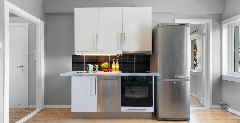 Lyst kjøkken med medfølgende hvitevarer.