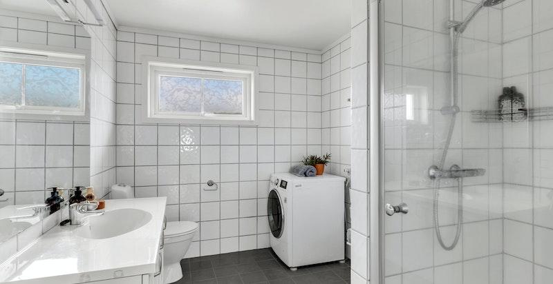 Badet inneholder dusjnisje, toalett og opplegg for vaskemaskin.