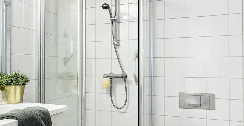 Flislagt gjestebad med dusj og varmekabler i gulvet