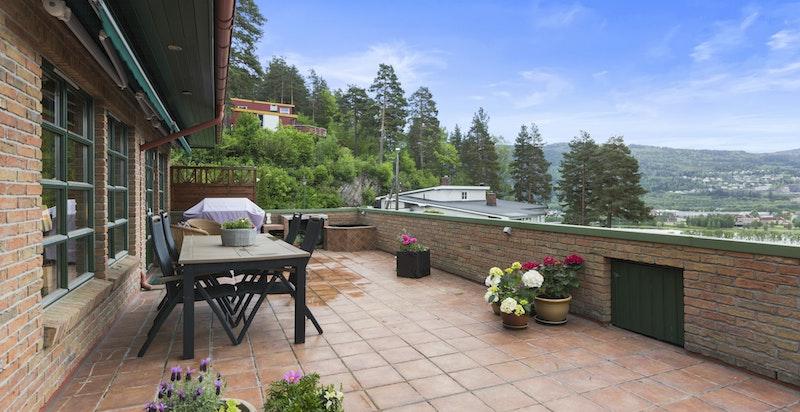 Fra stuen er det direkte utgang til flislagt terrasse med epoxbelegg på hele 82 kvm med panorama utsikt