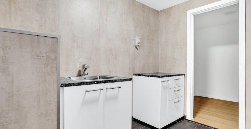 Boligen byr på eget vaskerom, med innredning og flislagt gulv, videre ser man en av boligens to boder.