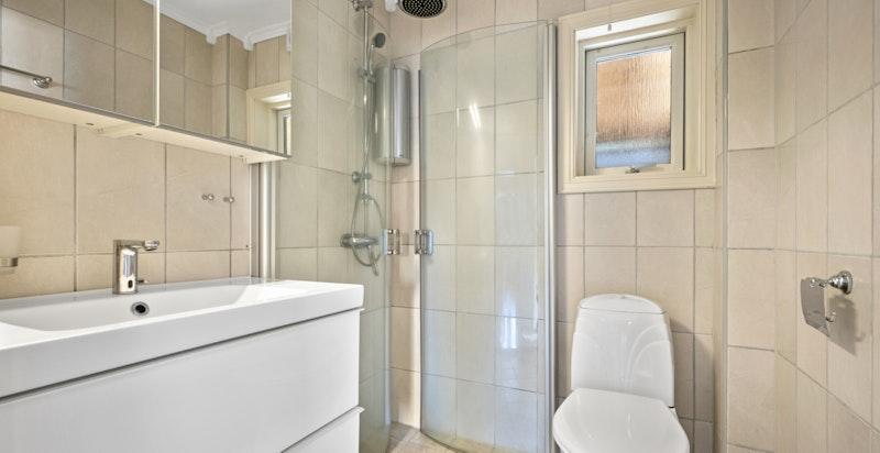 Flislagt bad med gulvstående klosett og dusjnisje. Varmekabel i gulv.