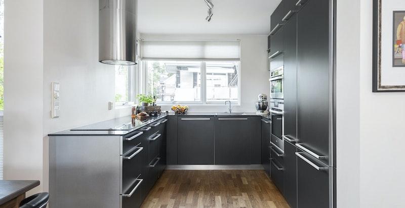 Flott designet kjøkken med koksgrå slette fronter og benkeplate i stein