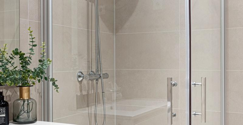 Vegghengt toalett, dusjhjørne med innfellbare dusjvegger i glass og opplegg for vaskemaskin/tørketrommel.