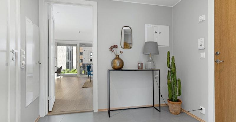 Flott entré med storformat-fliser på gulv og plass til innredning.