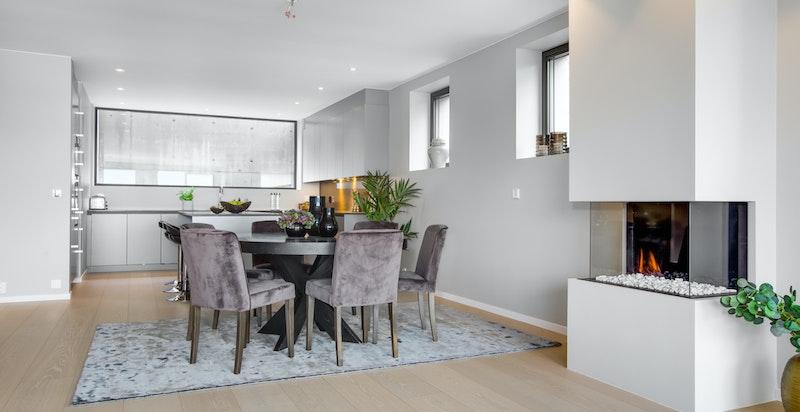 Kjøkkenet ligger i åpen løsning med stuen, og sentralt i rommet er det en moderne gasspeis