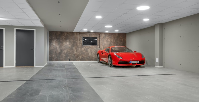 I kjelleren er det et moderne garasjeanlegg, og det medfølger to biloppstillingsplasser