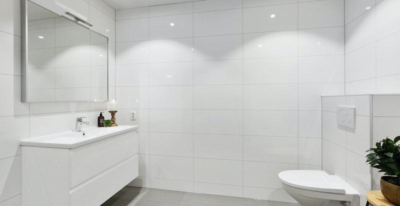Flislagt bad i underetasjen med varmekabler og vegghengt toalett