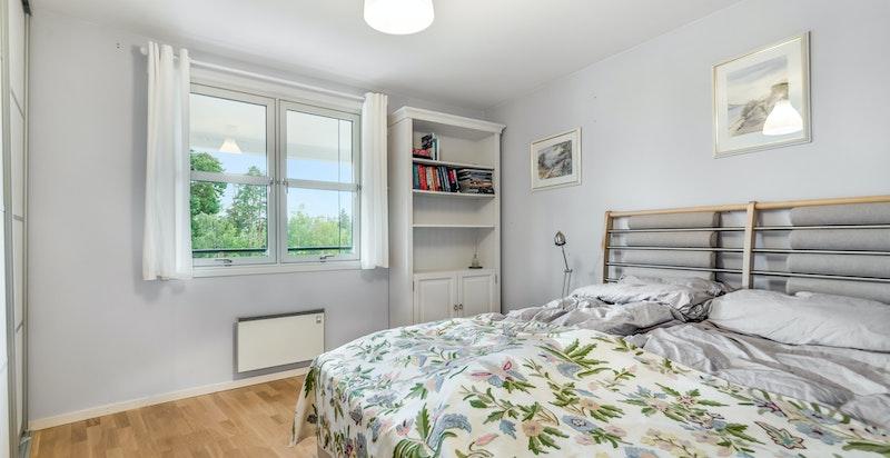 Lyst soverom med god plass til dobbelt seng og romslig skyvedørsgarderobe.