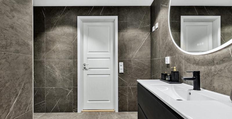 Veggmontert dusj og klosett, servant i underskap i bad. Opplegg til vaskesøyle. Lys innfelt i himling og integrert i speil. Mulighet for å sette inn badekar