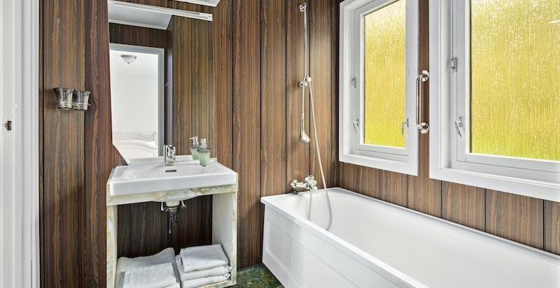 Badet er fra byggeår med varmekabler i gulv. Innredning med underskap, speil og lys. Badekar med blandebatteri og dusjhode