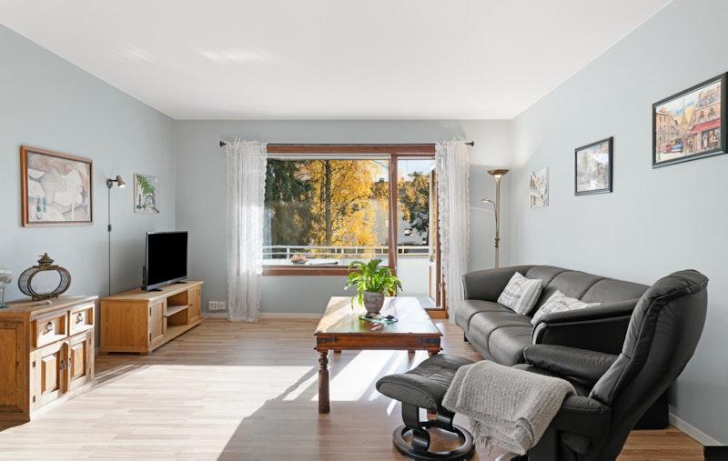Stort stueareal med utgang til balkongen. Store vindusfalter bidrar med naturlig lys inn i rommet.