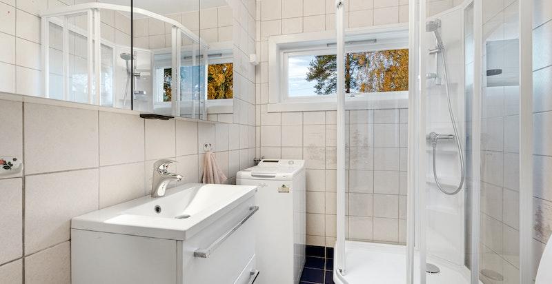 Baderom med varme i gulv, dusjkabinett, servant med underskap, opplegg for vaskemaskin og toalett.