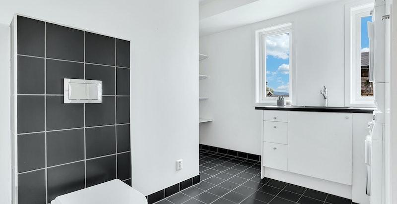 Boligens vaskerom inneholder vegghengt wc og opplegg for vaskemaskin
