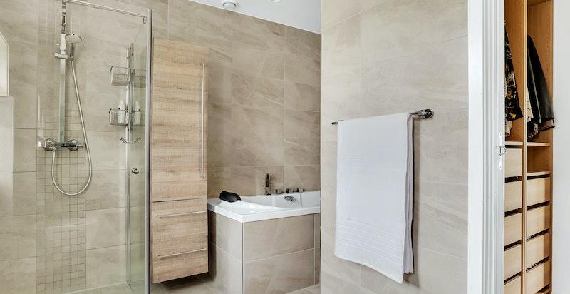Baderommet er innredet med dobbelservant, vegghengt wc, dusjhjørne med glassdører og innebygd badekar