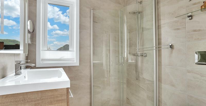 Lekkert flislagt bad med varmekabler i gulv.