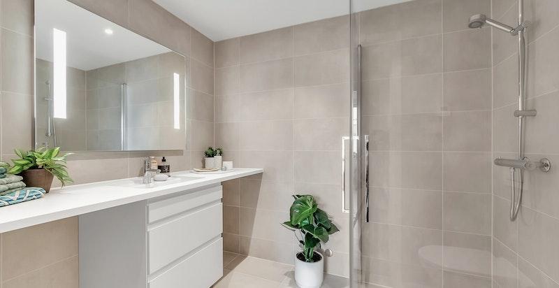 Pent bad 2/vaskerom med veggmontert wc og skjult sisterne, laminert benkeplate med underlimt porselensservant og dusjhjørne med glassdører