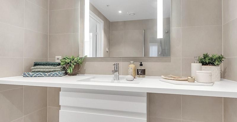 Begge badene i leiligheten er flislagt i tidsriktige og pene farger