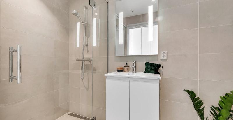 Delikat dusjbad/wc med veggmontert wc og skjult sisterne, servant med baderominnredning og dusjnisje med glassdør