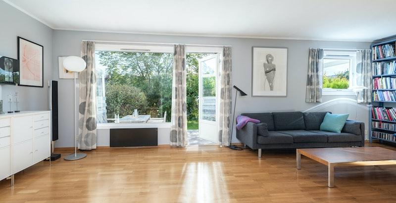 Stuen har store vinduer som gir et lyst inntrykk av boligen