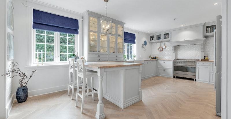 Kjøkkenet har en moderne barløsning, slik at barna eller gjestene kan følge kokkens håndlag på nært hold fra andre siden av benken.