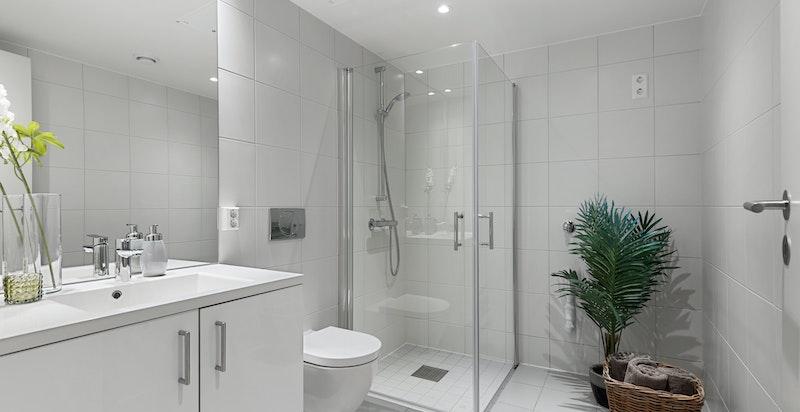 Flott flislagt bad med opplegg for vaskemaskin og tørketrommel.