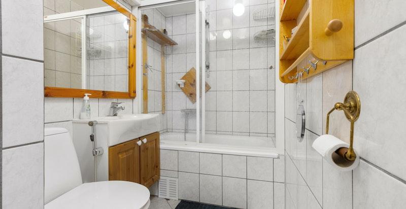 Bad med badekar og dusj, vaskesøyle med opplegg for vaskemaskin og tørketrommel