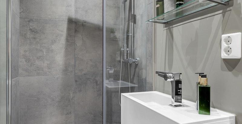 Bad/wc inn fra entré/hall med varmekabler i gulv. dusjhjørne med innfellbare dusjdør, veggmontert wc, elektrisk avtrekksvifte i himling, veggmontert servant med blandebatteri