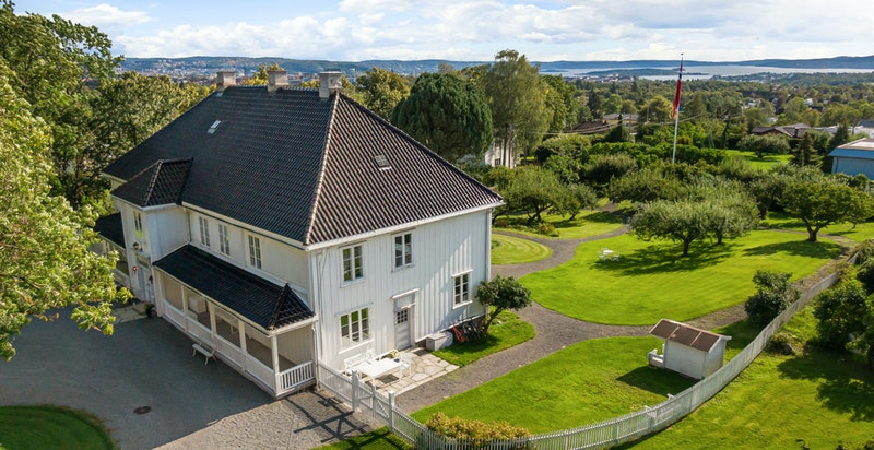 Oversiktsbilde av hovedhuset fra vest. Den vakre utsikten mot Bunnefjorden kan nytes fra annenetasjens sydvestlige stue og soverom