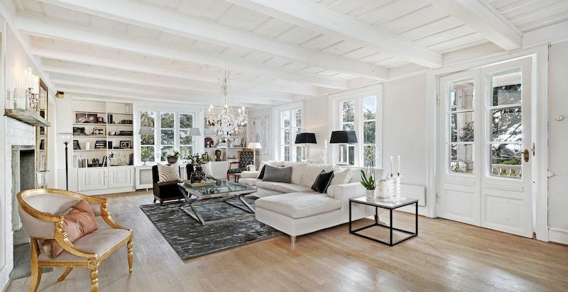 Stor solfylt og luftig stue med utgang til veranda. Vinduene i hele annenetasjen har gamle verdifulle kulturglass, som vitner om husets historiske sus