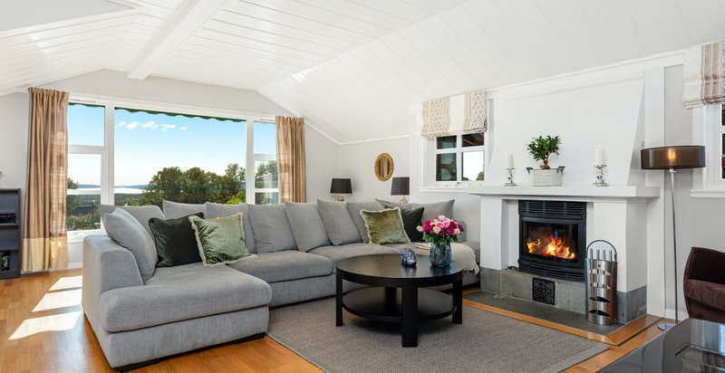 Romslig stue med store vindusflater med hyggelig utsikt. Peis.