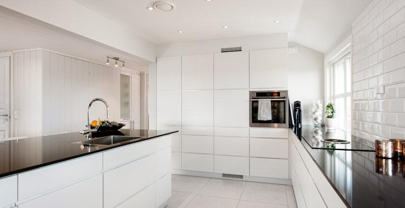 Kjøkkenet har mye lagringsplass og rikelig med benkeplass