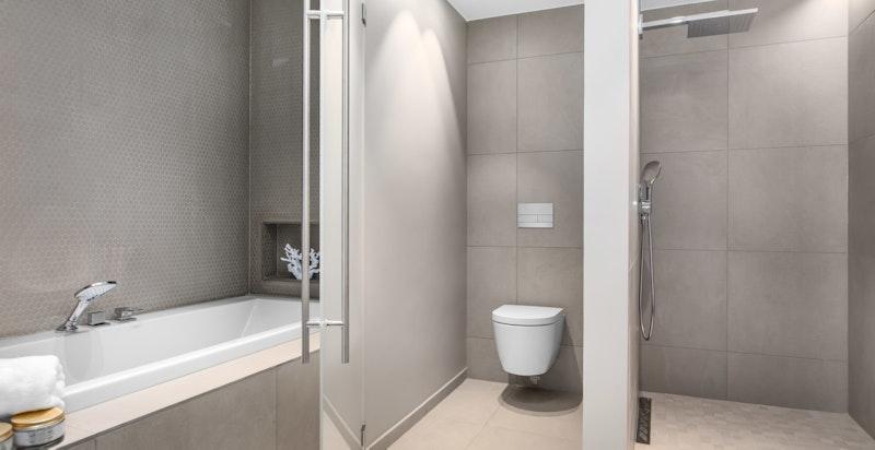 Badet har egne nisjer til badekar, toalett og dusj begge med dør i frostet glass.