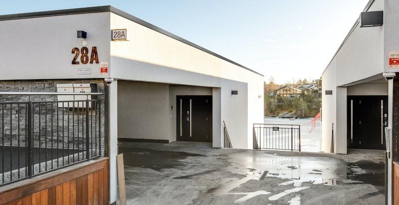 Garasjeplassene sees til venstre i bildet med leilighetens inngangsparti.