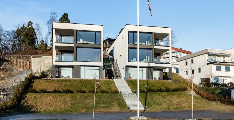 Leiligheten er i de 2 øverste etasjene i bygningen til høyre i bildet.