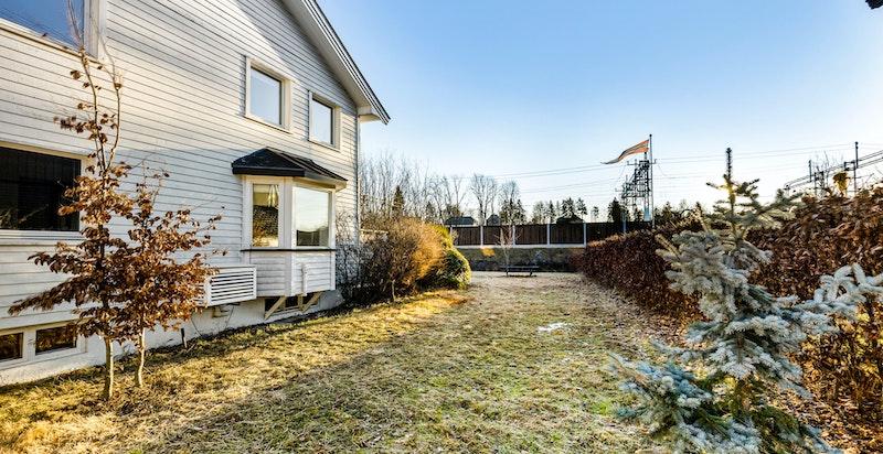 Tomten er opparbeidet med innkjørsel, gårdsplass, terrasse, beplantning og gressplen.