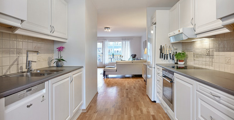 Pent kjøkken som er oppgradert i nyere tid med malte skapfronter, ny oppvaskmaskin og ny kjøl-/fryseskap
