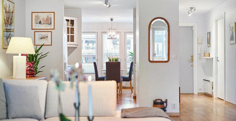 Detaljbilde fra stuen mot kjøkken og spisestue - parketten i stue, kjøkken og entréen er nyslipt i nyere tid