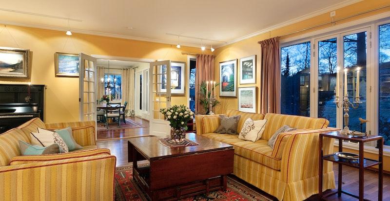 Stue med store vindusflater og videre adkomst til kjøkken