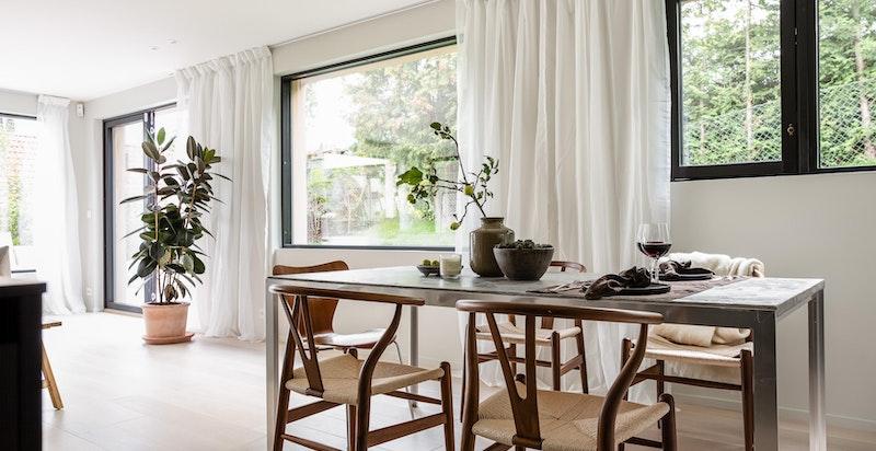 Lys spisestue i åpen løsning mot kjøkken og stue