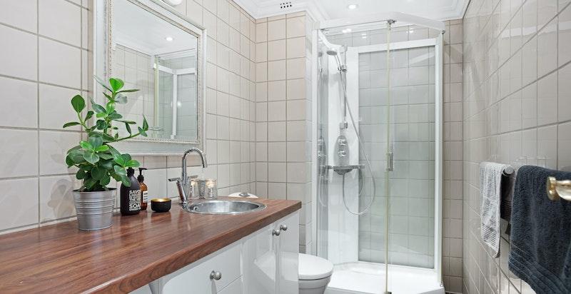Hyggelig baderom innredet med servantskap, toalett og dusjkabinett
