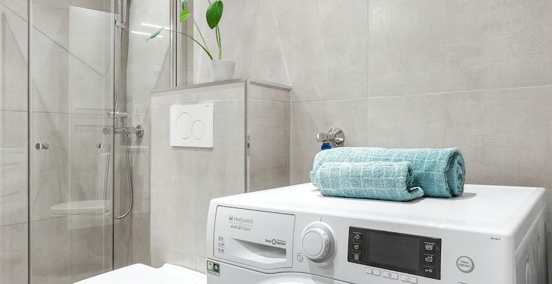Delikat bad med opplegg for vaskemaskin, vegghengt toalett og dusjnisje.